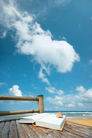 composition vertical: Prenota con una conchiglia sulla sedia di bamb� in spiaggia. Composizione verticale.