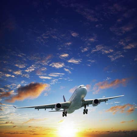 비행: 일몰 시간에 하늘에서 제트 비행기. 광장 조성. 스톡 사진