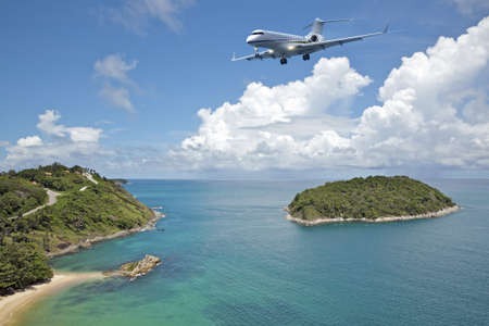 Private jet plane is going to land at the airport of a tropical island. Luxury style living concept.  photo
