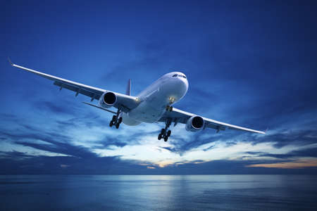plane landing: Jet plane over the sea at dusk Stock Photo