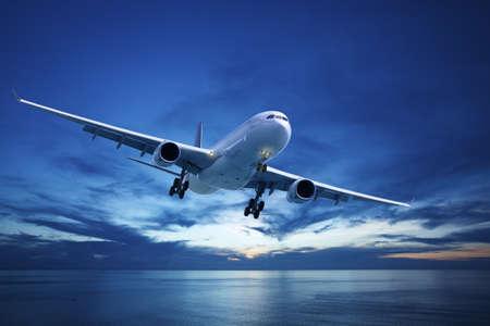 Jet vliegtuig over de zee in de schemering