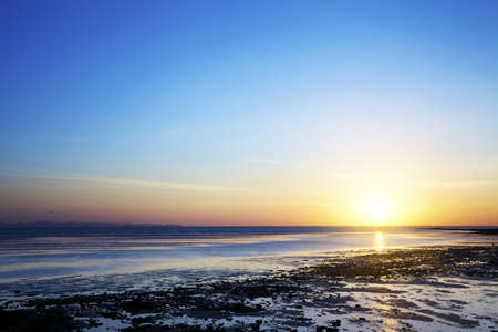 low tide: Sunrise over the beach at low tide Stock Photo