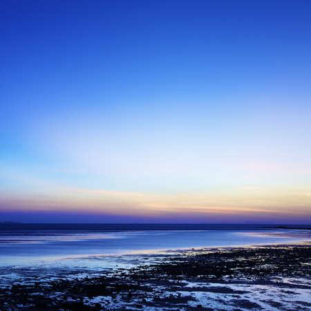plan éloigné: Lever de soleil sur la plage à marée basse. Composition carrée. Tir longue exposition. Banque d'images