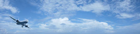 Jet plane in a blue cloudy sky. Panoramic composition in high resolution. photo