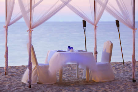 restaurant setting: A good place for romantic dinner on the beach  Long exposure shot  Focused on a dishware, shallow DOF