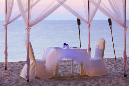 diner romantique: Un bon endroit pour un dîner romantique sur la plage de l'exposition Long Shot focalisés sur une vaisselle, shallow DOF Banque d'images