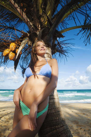 Young woman relaxing under the palm tree. Vertical shot. photo