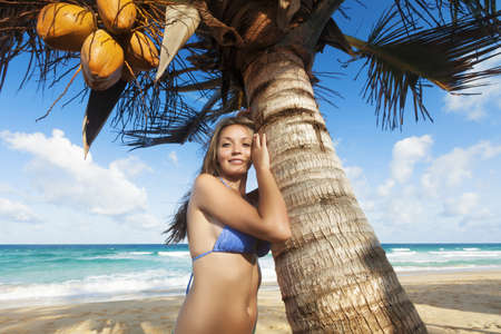 Young woman relaxing under the palm tree photo