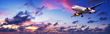 maneuvering: Jet aircraft is maneuvering for landing in a spectacular sunset sky. Panoramic composition.