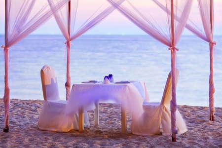 ビーチでロマンチックな夕食のための良い場所。長時間露光ショットします。食器、浅い自由度に焦点を当てた。 写真素材