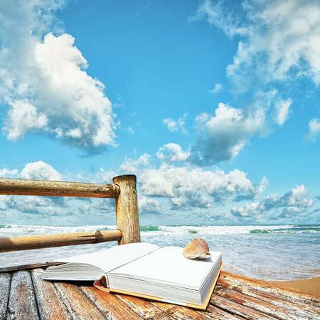 Książka z muszli na bambusowym krześle na plaży. Kwadrat Skład.