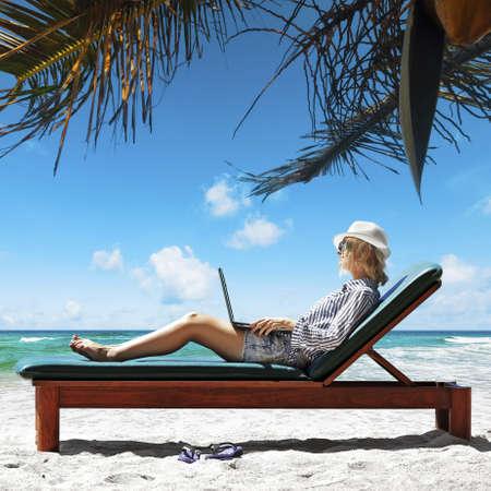 Jonge vrouw met een laptop onder de palmboom Stockfoto