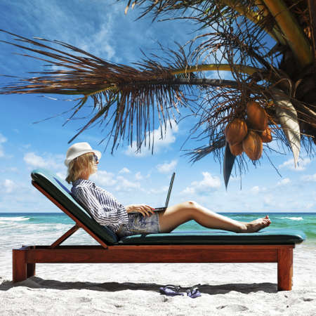 Young woman with laptop at the beach Standard-Bild