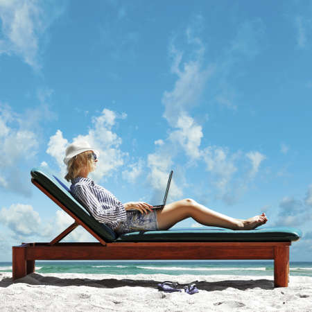 Young woman with laptop on the beach photo