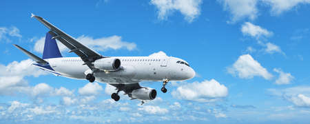 airplane landing: Jet plane in a blue cloudy sky. Panoramic composition. Stock Photo