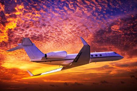 Private jet cruising in a sunset sky Standard-Bild