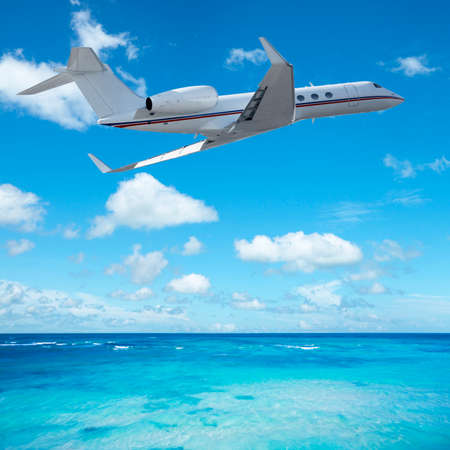 first plane: Private jet plane over the tropical sea