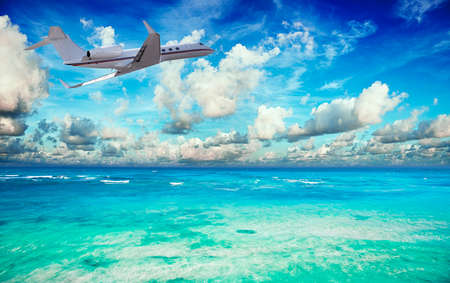 private jet: Private jet over the tropical sea Stock Photo