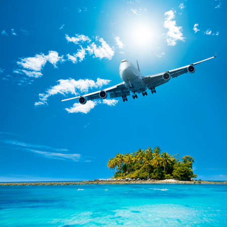 airplane landing: Tropical vacation with plane flying Stock Photo