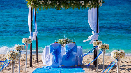 Decorated wedding table on the beach, soft evening light photo