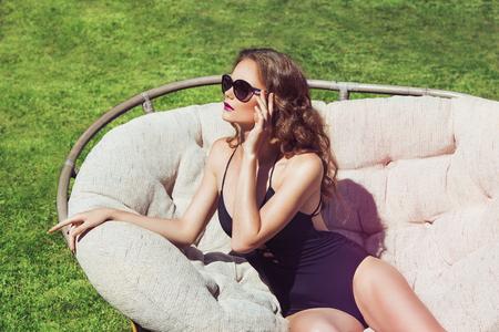 junge nackte m�dchen: Sch�ne braune Haare Frau tr�gt Bikini. Junges M�dchen Modell im eleganten schwarzen sexy Badeanzug der W�sche in einer Kappe. Voller Entspannung. Jahrgang. Sonnenbad auf einer Liege. Lizenzfreie Bilder