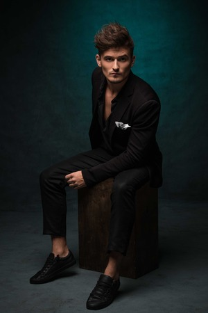 3 persons only: Beautiful athletic bodybuilder male model posing in studio. Expression on camera. Brutal man in leather suit. Stock Photo