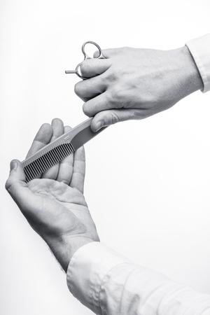 The steel scissors and comb in hairstyler hands