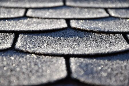 Roof with asphalt shingles is frostbitten. Frost.