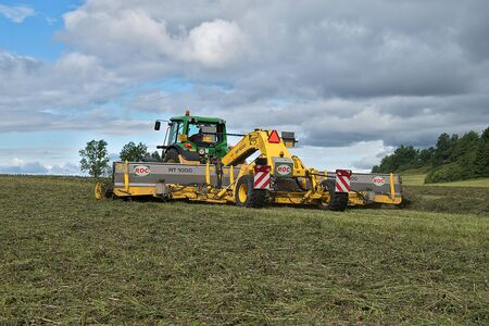 Svitavy, Czech Republic - 20.4.2019: Forage harvest. John Deere tractor rows clover with ROC RT 1000 crawler rake. Agricultural field work