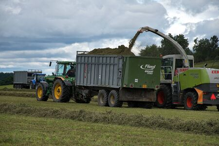 Svitavy, Czech Republic - 20.4.2019: Forage harvest. The John Deere tractor and Claas are harvesting clover for haylage. Agricultural field work