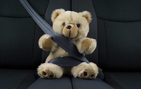 Teddy bear is sitting in a car fastened with a seat belt, represents a child safety in a car