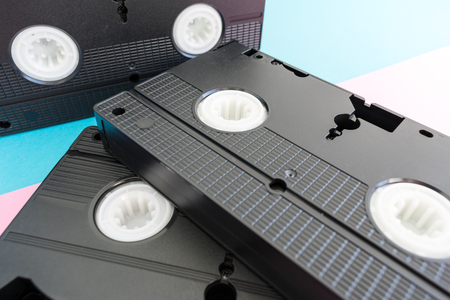 Close-up on 3 black  video tapes on a and blue background.