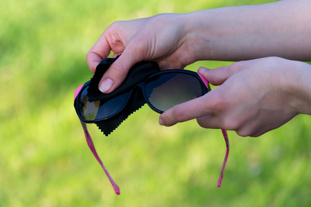 Female hands cleaning sunglasses outdoors