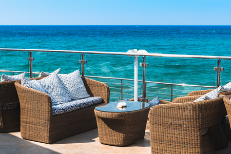 Stock Photo   View On An Empty Luxury Balcony Near The Sea With Rattan  Furniture.