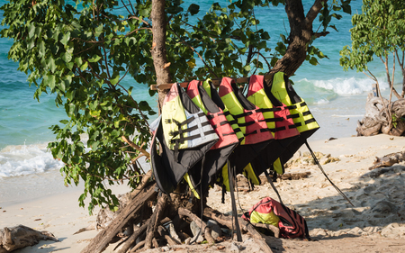 Colorful life jackets hanging on a rack on a tropical beach. Equipment for active water sports. Stock Photo