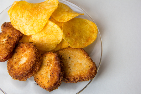Nuggets and yellow chips in transparent glass plate