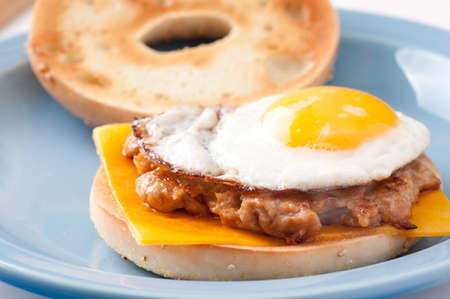 fried sunnyside up egg on a sausage patty with a bagel and cheese
