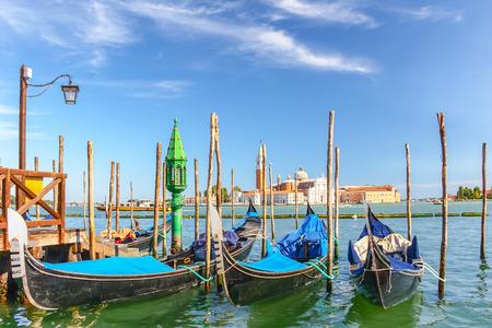 Gondolas moored by Saint Mark square with San Giorgio di Maggiore church in the background, Venice, Italy