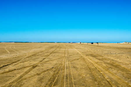very big sand space with a blue background sky