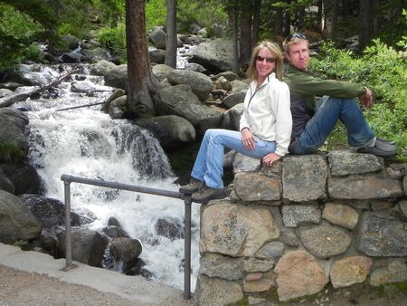 A mother and son sitting next to each other on top of rocks next to a babbling creek