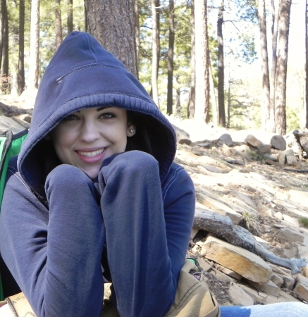 A young, pretty woman in a forest wearing a hoodie