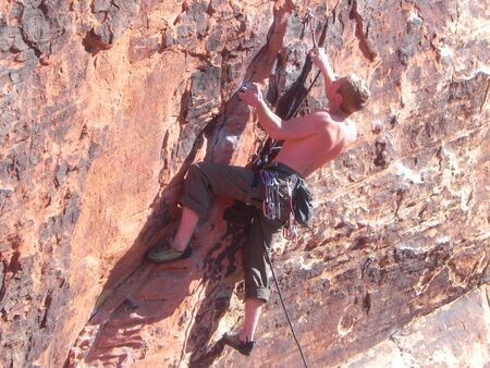 A young, athletic man climbing a sheer wall Imagens