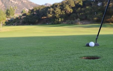 ゴルフ場のパッティング グリーンに穴にゴルフボールを置くこと