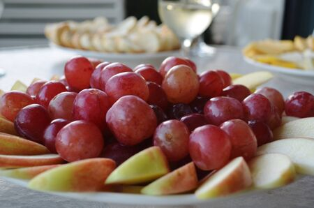 Red grapes arranged on top of sliced apples on a plate Stock fotó