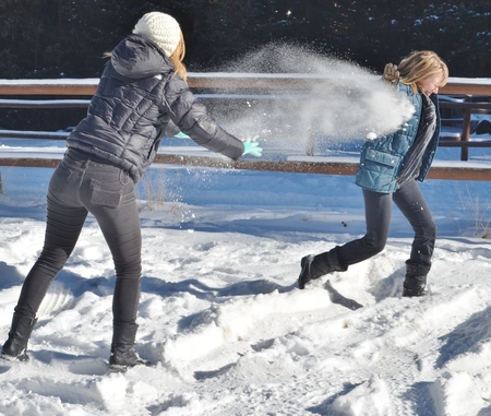 powdery: Two young, attractive women throwing white, powdery snow at each other.