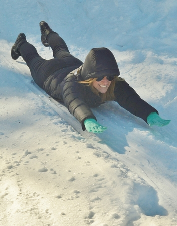 A young, attractive woman laughing while sliding down a snowy hill on her stomach.