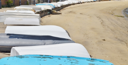 turned out: A long row of different colored boats lined up on a concrete landing next to a sandy beach.  The boats are all turned upside down and the tide is out. Stock Photo