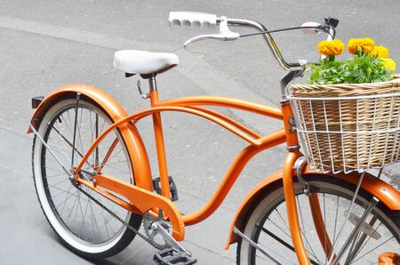 handlebars: A bright orange bicycle with a wicker basket full of colorful yellow geraniums.  The bike has a matching white seat and white grips on the handlebars.
