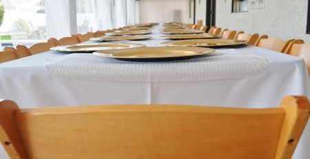 table: A long table located on an outdoor patio set for a wedding rehearsal dinner for 75 people.  The plates are white with gold trim and a white tablecloth covers the table.  The chairs are made of wood. Stock Photo