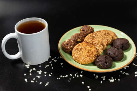 Tasty chocolate cookies with a tea cup on the black background Banque d'images